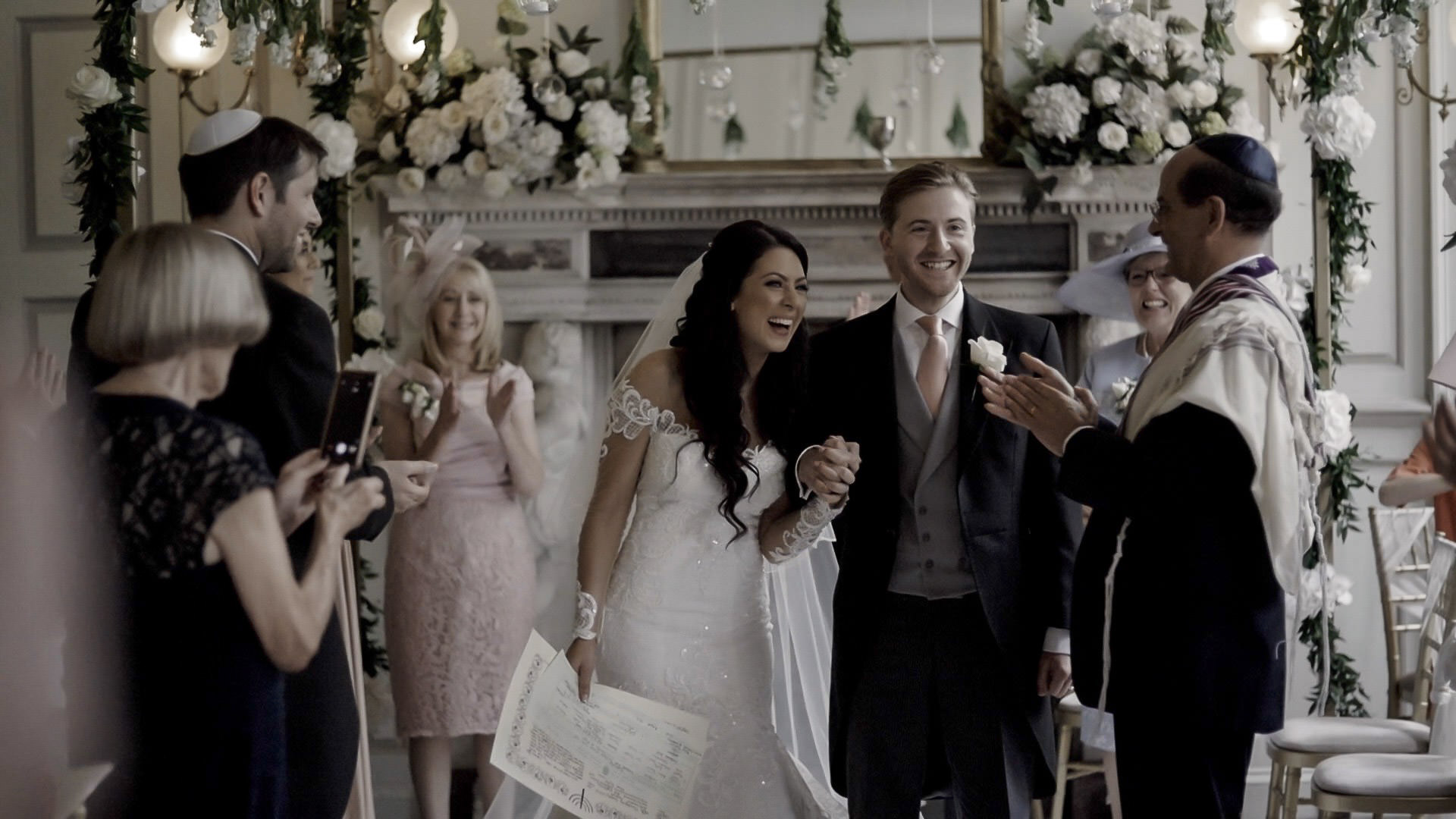 An Image from Natasha and Adam's Gosfield Hall Wedding Video showing the couple walking down the aisle.