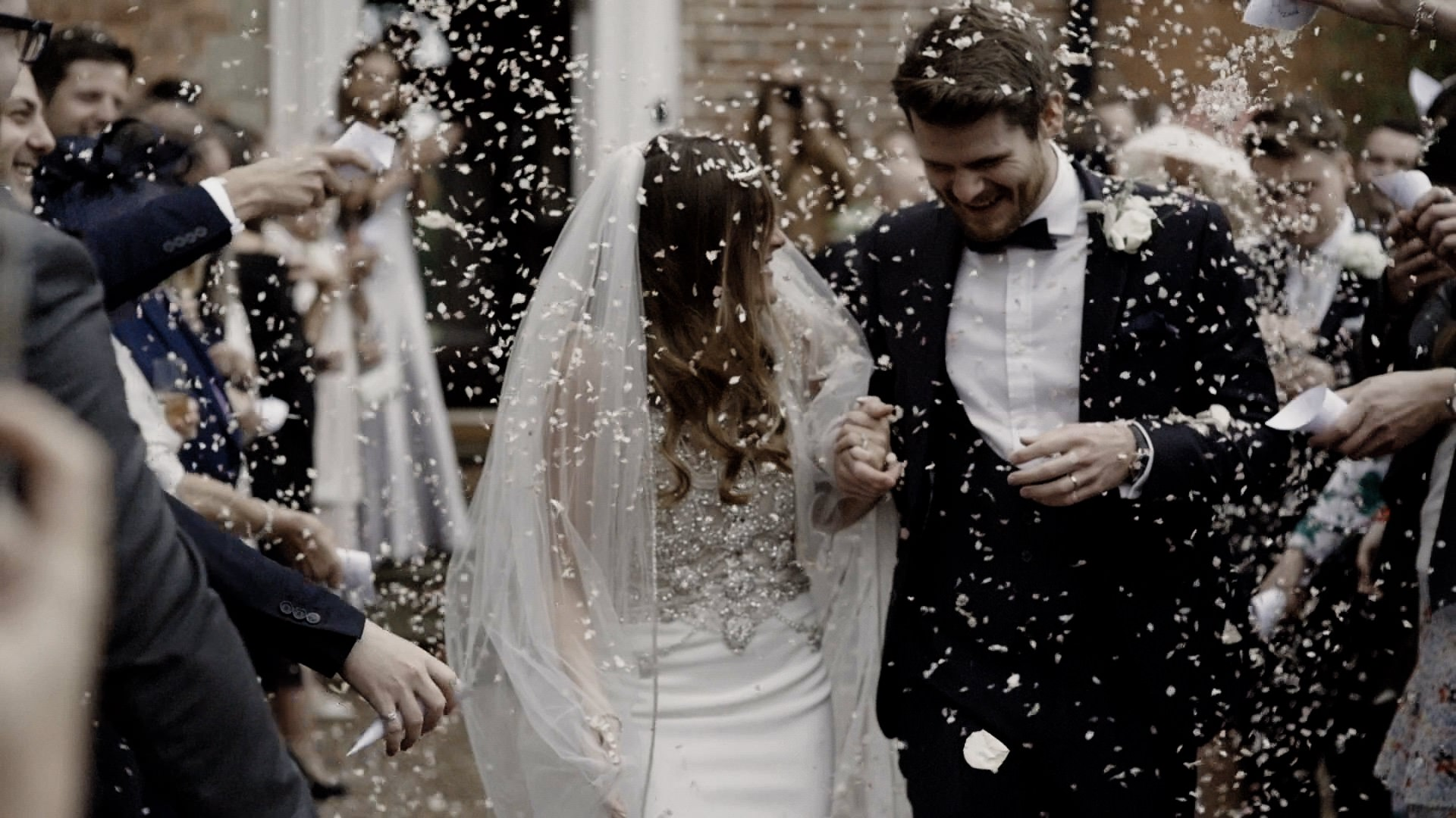 A Freeze Frame from Victoria and Craig's Iscoyd Park Wedding Video. The couple emerge from the venue to a shower of confetti.