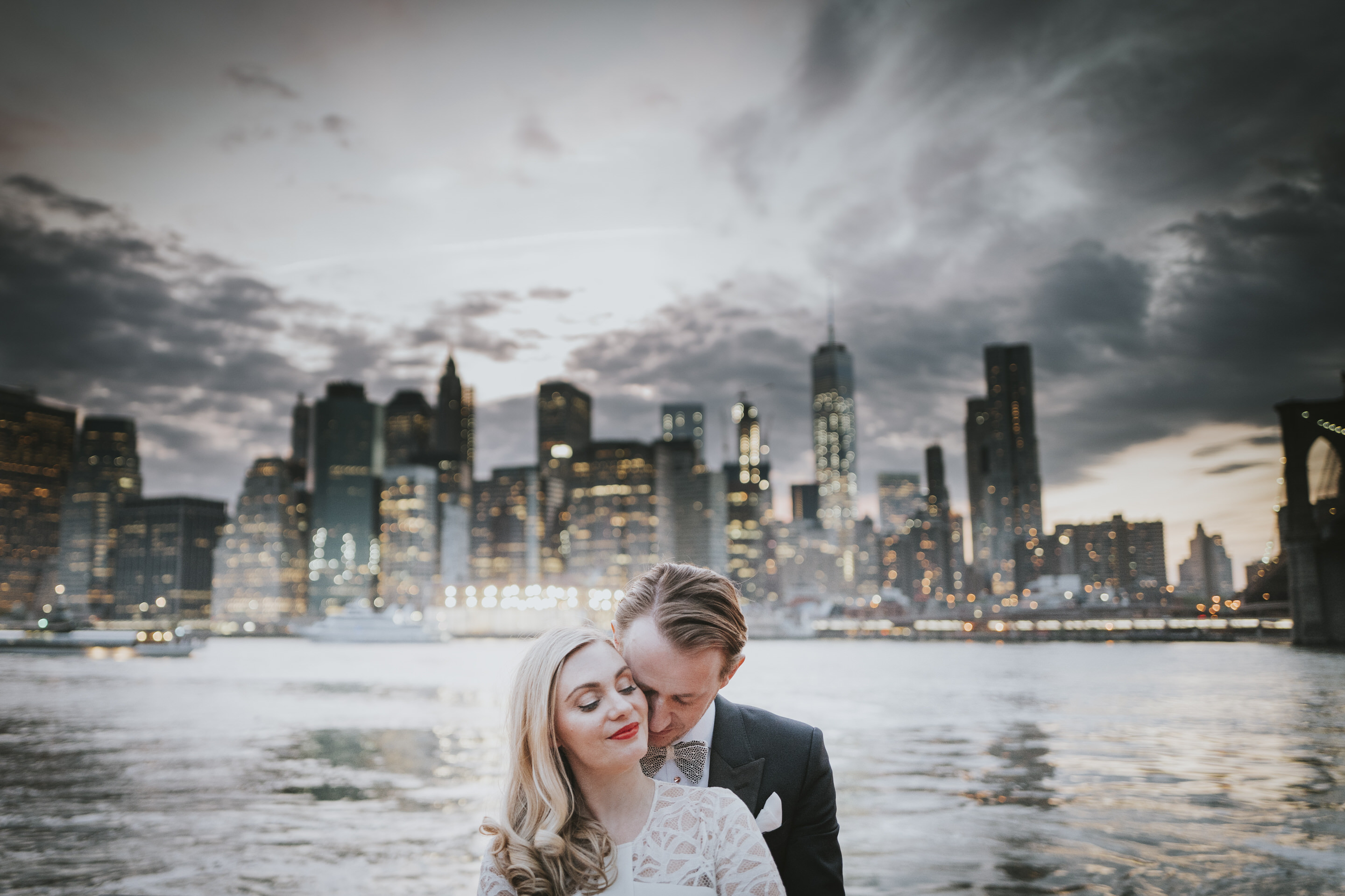 Newlyweds spend a quiet moment together beneath the Manhatten Skyline.