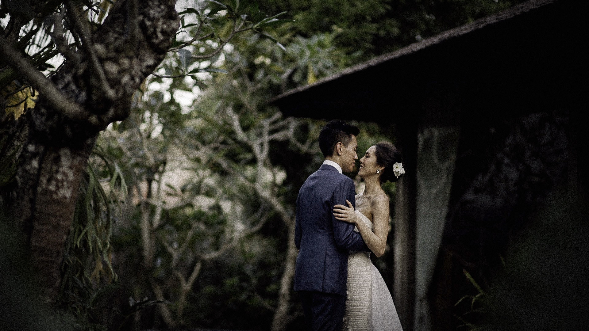 A freeze frame from one of my favourite Bali Wedding Videos. A young newly web couple kiss outside their wedding venue.