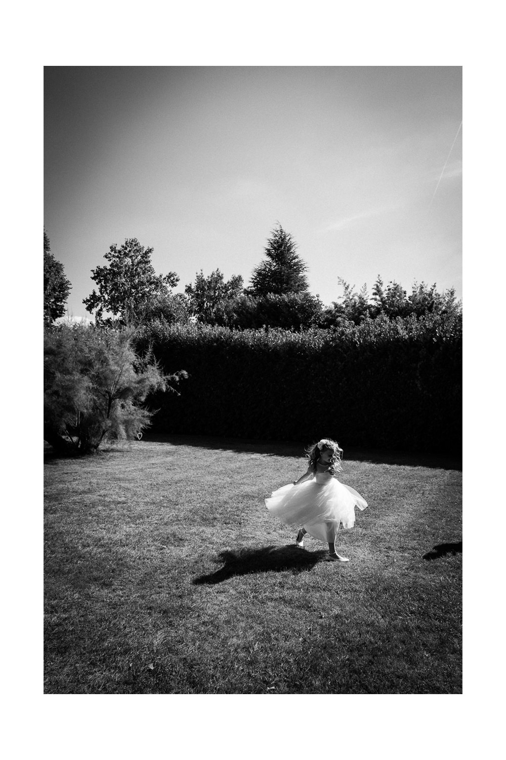 a young bridesmaid dances in a garden. A frame from my recent uk wedding videography work.