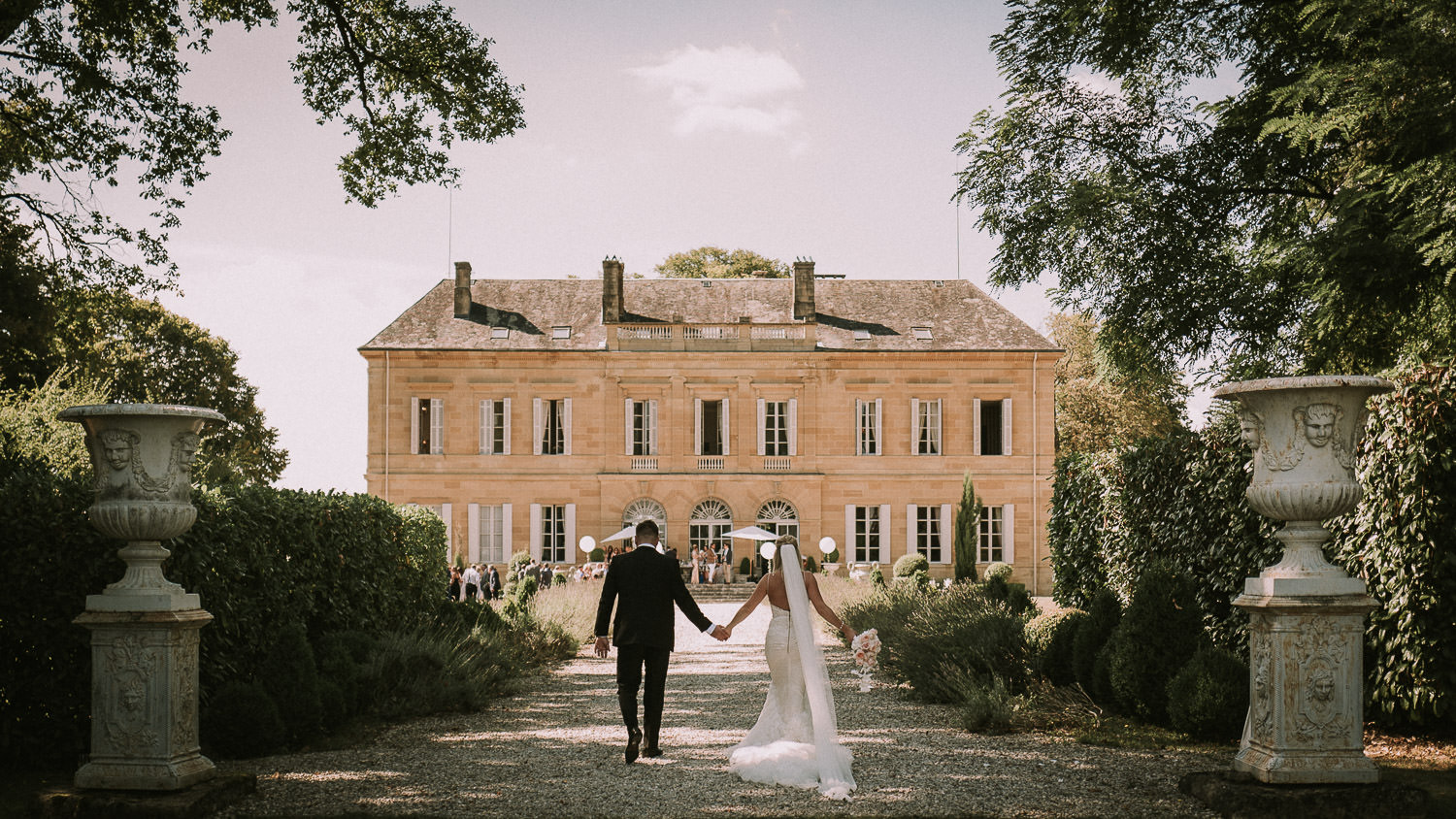 A couple walk towards their chateau from one of my weddings in France.