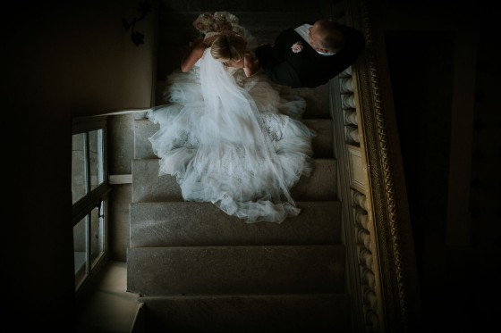 a photograph from above a very old stone staircase shows a bride and her father walking to the wedding ceremony.