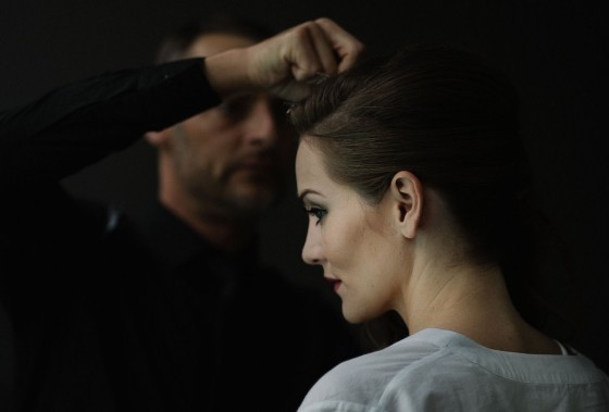 a male hairdresser make some final adjustments to a brides hair.