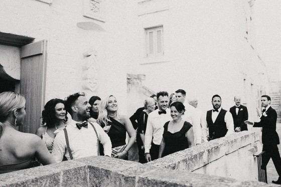 a group of a few dozen wedding guests laugh together as they enter an Italian church.