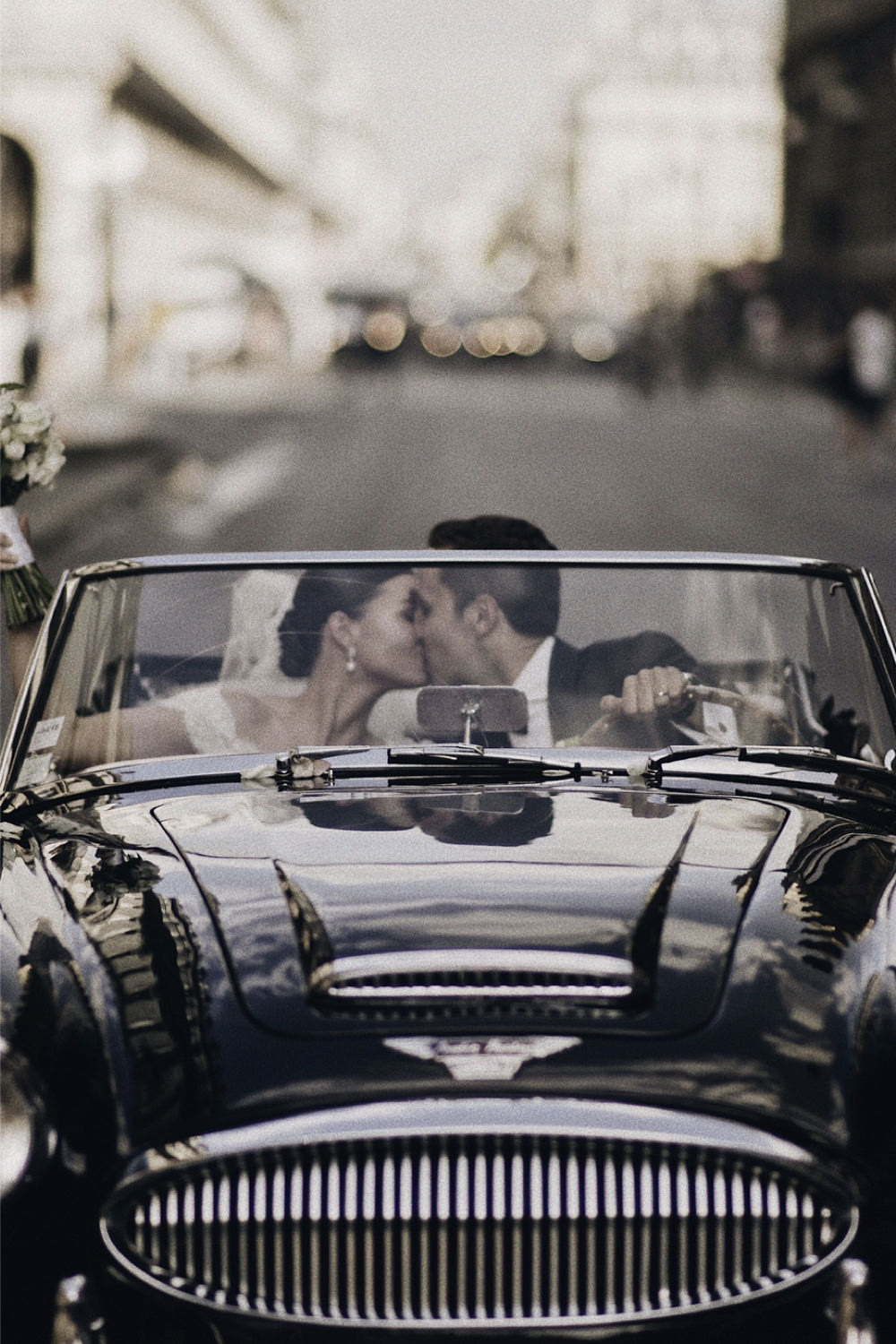 A couple drive off in their wedding car in Paris.