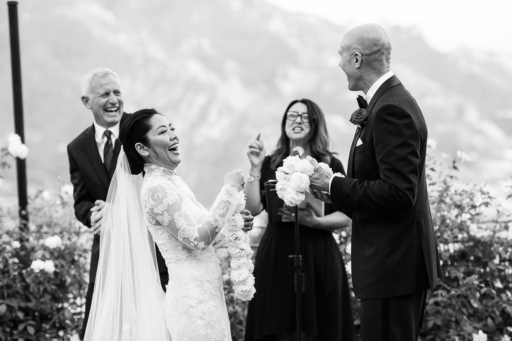 Belmond Caruso Wedding Photographer Philip White captures a fun moment where the bride groom and celebrant or all laughing together.
