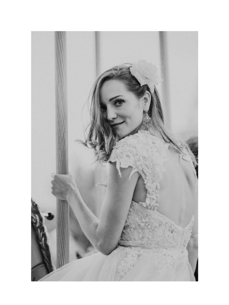 a bride riding a carousel looking back towards the camera.